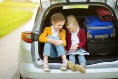 2 прелестных маленькой девочки сидя в автомобиле перед идти на каникулах с их родителями 2 дет смотря вперед для поездки Стоковое Изображение