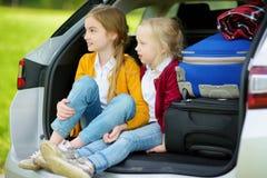 2 прелестных маленькой девочки сидя в автомобиле перед идти на каникулах с их родителями 2 дет смотря вперед для поездки Стоковое Изображение RF