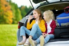 2 прелестных маленькой девочки сидя в автомобиле перед идти на каникулах с их родителями 2 дет смотря вперед для поездки Стоковая Фотография RF