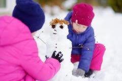 2 прелестных маленькой девочки строя снеговик совместно в красивом парке зимы Милые сестры играя в снеге Стоковые Фотографии RF
