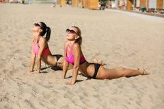 2 прелестных модели фитнеса нося стекла и йогу купальника практикуя со стоковые фотографии rf