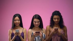 3 прелестных multiracial женщины используя мобильные приложения и смотрящ вверх, шаблон акции видеоматериалы