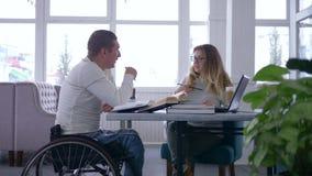 Преподавательство для инвалидного, счастливого больного мужчины студента в кресло-коляске с женщиной воспитателя во время дома из сток-видео