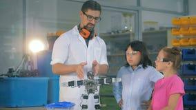 Преподаватель точных наук школы показывает умным ребеятам школьного возраста technolgies робототехники