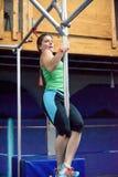 Препятствие поляка сильной женщины хватая с рукой и ногами стоковое изображение