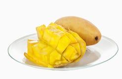 Прерванное манго половинное crosswise, лежащ на стеклянной пластинке на предпосылке всего манго Стоковое Изображение RF