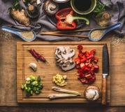 Прерванные овощи для stir жарят варить на деревянной разделочной доске на предпосылке с ингридиентами, взгляд сверху кухонного ст Стоковые Изображения RF