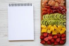 Прерванные плодоовощи аранжировали на разделочной доске и блокноте на белой деревянной предпосылке, крупном плане Плоское положен Стоковая Фотография