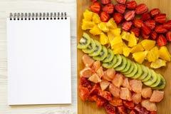 Прерванные свежие красочные плодоовощи аранжировали на разделочной доске с блокнотом на белой деревянной предпосылке, крупном пла Стоковые Изображения
