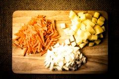 Прерванные луки, моркови, картошки штабелированные в группах на деревянном Стоковое фото RF