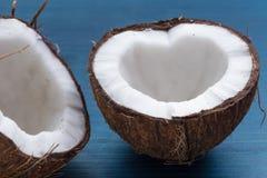 Прерванный кокос: половины кокоса в форме сердца на голубом Стоковые Фотографии RF