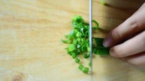 Прерывать лук весны на деревянной доске сток-видео