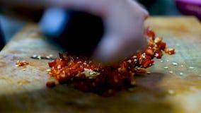 Прерывать перец красного chili на cuting доске в кухне сток-видео