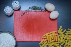 Прерывая доска кашевара и еды для варить: мука, макаронные изделия, яичка, соль, перец, тимиан Стоковые Изображения RF