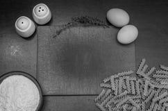 Прерывая доска кашевара и еды для варить: мука, макаронные изделия, яичка, соль, перец, тимиан Стоковое Фото