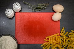 Прерывая доска кашевара и еды для варить: мука, макаронные изделия, яичка, соль, перец, тимиан Стоковые Фото