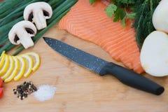 Прерывая доска с томатом, петрушка и сырцовые семги на разделочной доске Solt перчат, лимон Стоковая Фотография RF