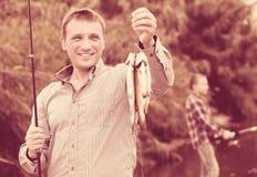Пресноводная рыба задвижки удерживания рыболова на реке Стоковые Изображения RF