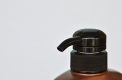 Пресса головы насоса бутылки шампуня на белой предпосылке Стоковые Фото