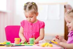 Прессформа детей от глины в комнате игры preschool Стоковые Изображения