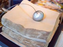 Пресс-папье дизайна металла на стоге коричневых салфеток стоковые фото