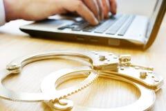 Преступление в компьютерной сфере Человек с компьтер-книжкой и наручниками исследование стоковое фото rf