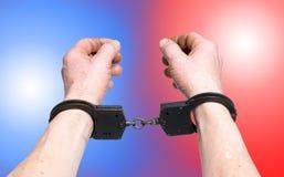 Преступник арестованный полицией Руки в наручниках над ligh полиции стоковое фото