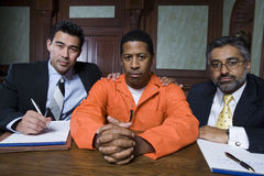 Преступник и юристы сидя в зале судебных заседаний Стоковая Фотография