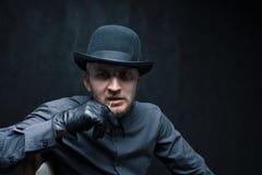 Преступник с шляпой и перчатки на темной предпосылке Стоковые Фотографии RF