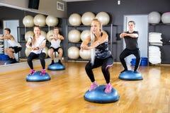 Преданная группа тренирует сидения на корточках на половинном шарике на спортзале фитнеса стоковые фотографии rf