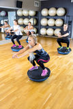 Преданная группа тренирует сидения на корточках на половинном шарике на спортзале фитнеса стоковые фото