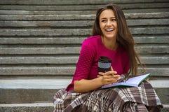 Прелестная девушка делает показатели в дневнике сидя на лестницах Стоковые Изображения