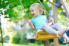 Прелестная девушка имея потеху на качании на летний день Стоковая Фотография