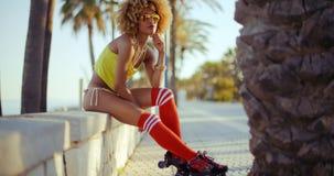Прелестная девушка конька ролика сидя на пляже Стоковые Фото