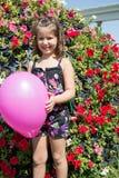 Прелестная девушка маленького ребенка в парке около цветника в летнем дне Стоковое Фото