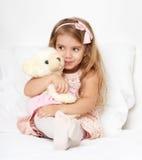 Прелестная девушка маленького ребенка сидит в кровати с ее игрушкой Девушка ребенка обнимает плюшевый медвежонка Стоковое Изображение RF