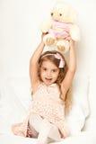 Прелестная девушка маленького ребенка сидит в кровати с ее игрушкой Девушка ребенка обнимает плюшевый медвежонка Стоковая Фотография