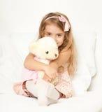 Прелестная девушка маленького ребенка сидит в кровати с ее игрушкой Девушка ребенка обнимает плюшевый медвежонка Стоковое фото RF