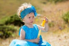 Прелестная девушка маленького ребенка с воздуходувкой пузыря на траве на луге Природа лета зеленая Стоковые Фото