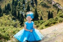 Прелестная девушка маленького ребенка с воздуходувкой пузыря на траве на луге Природа лета зеленая Стоковые Фотографии RF