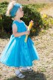 Прелестная девушка маленького ребенка с воздуходувкой пузыря на траве на луге Природа лета зеленая Используйте его для concep мла Стоковая Фотография
