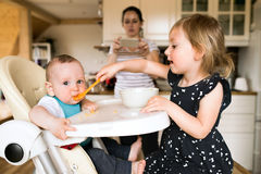 Прелестная девушка малыша дома подавая ее брат младенца Стоковая Фотография RF