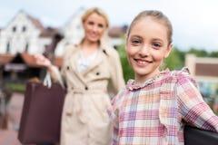 Прелестная девушка при ее мать стоя с хозяйственными сумками и смотря камеру на улице Стоковые Изображения RF