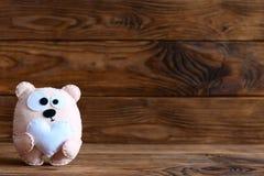 Прелестная игрушка медведя войлока с сердцем Игрушка плюшевого медвежонка изолированная на коричневой деревянной предпосылке с пу Стоковые Изображения