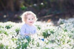 Прелестная курчавая девушка малыша в первой весне цветет Стоковое Фото