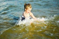 Прелестная маленькая девочка брызгающ и ломающ морскую воду и имеющ потеху Стоковое Изображение RF