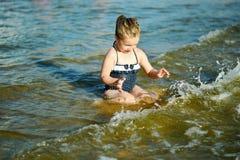 Прелестная маленькая девочка брызгающ и ломающ морскую воду и имеющ потеху Стоковая Фотография RF