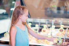 Прелестная маленькая девочка есть мороженое outdoors Милый ребенк выбирает gelato в итальянском gelateria стоковые изображения rf