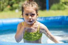 Прелестная маленькая девочка играя на открытом бассейне Стоковые Изображения RF