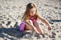 Прелестная маленькая девочка играя на пляже Стоковые Фотографии RF